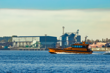 Orange pilot ship sailing past the factory in Latvia Stock Photo
