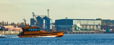 Orange pilot ship sailing past the factory in Latvia Stock Photo