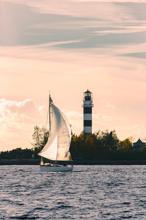 Sailboat moving past the big lighthouse in evening, Latvia Stock Photo