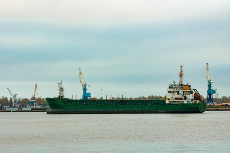 Green cargo ship moving to the port in cloudy day Stock Photo