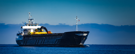 Black cargo ship with long reach excavator moving by baltic sea