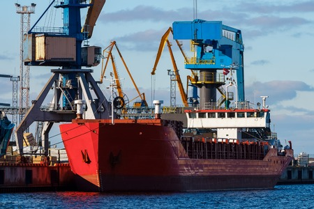 Red cargo ship loading in the port of Riga, Europe Stock Photo