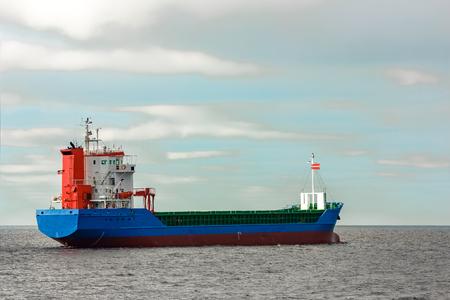 Blue cargo ship entering the Baltic sea. Riga, Europe