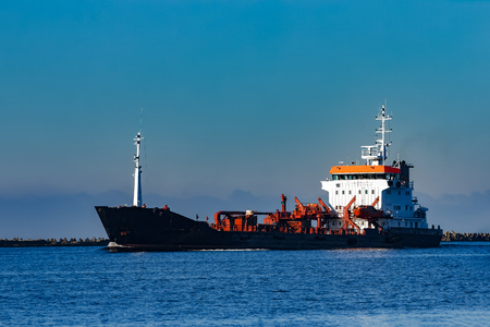 Black cargo oil tanker sailing in still water from Baltic sea