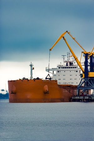 Large orange cargo ship loading with a coal in the port
