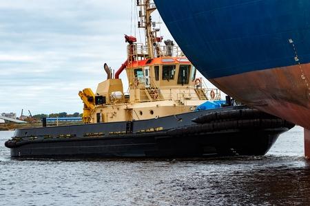bulk: Tug ship towing blue bulk carrier in the port of Riga Stock Photo