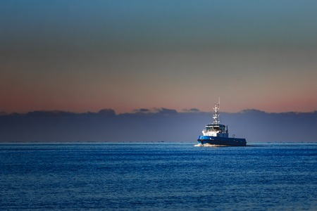 Blue small tug ship sailing from the Baltic sea in the morning Stock Photo