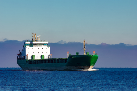Green cargo ship moving in still water of Baltic sea Stock Photo