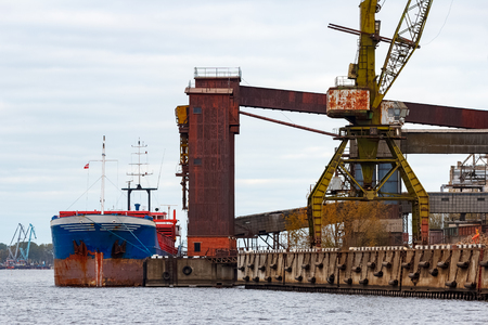 Blue cargo ship loading in the port of Riga, Europe