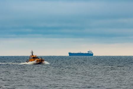 Orange pilot ship moving at speed in Baltic sea Stock Photo