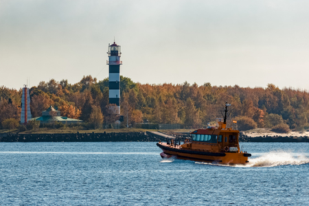 Yellow pilot ship moving at speed past the lighthouse in Riga