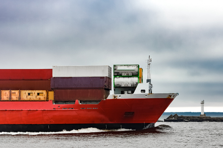 ship bow: Red cargo container ships bow in cloudy day Stock Photo