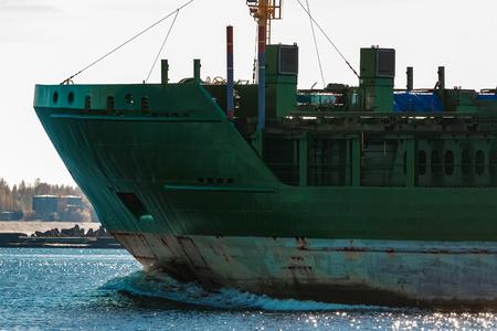 Green cargo ships bow close up in still water, Riga