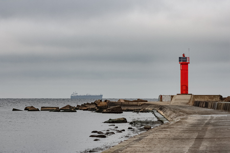Breakwater dam with red lighthouse in Riga, Europe
