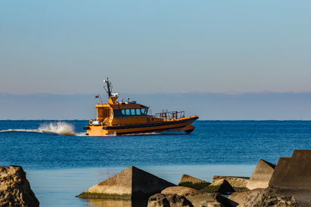Yellow pilot ship moving at speed past the breakwater dam