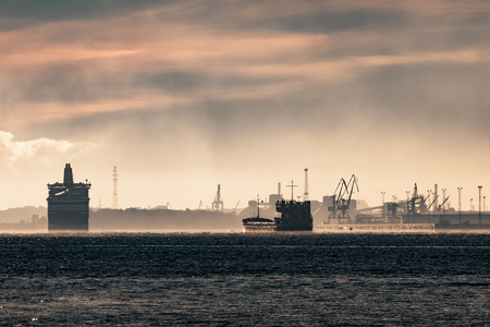 Cargo ship silhouette entering a port of Riga at the morning