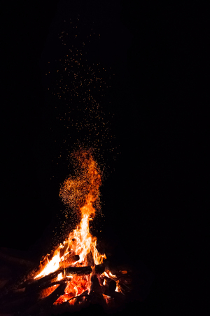Campfire with flying sparks isolated on black background