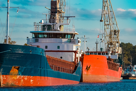 Blue cargo ship moored and loading at the port