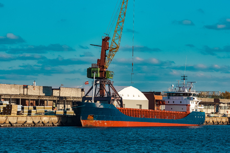 unloading: Blue cargo ship moored and loading at the port