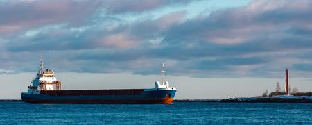 Blue bulk carrier sailing in still water