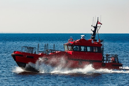 Red pilot ship moving from the Baltic sea