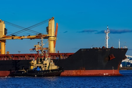Black cargo ship mooring at the port with tug ship support Stock Photo