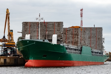 Green cargo ship loading in the port of Riga, Europe