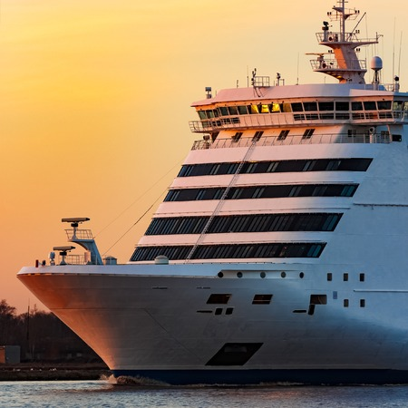 White passenger ship moving against the orange sunset sky