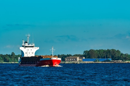 Red cargo ship fully loaded with wood moving at clear day Stock Photo