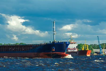 heavy industry: Blue bulk carrier moving in clear summer day