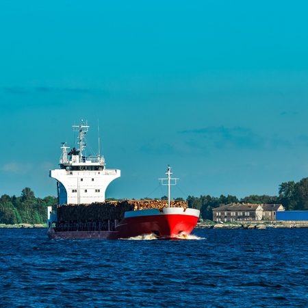 heavy industry: Red cargo ship fully loaded with wood moving at clear day Stock Photo