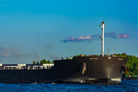 heavy industry: Black cargo ship moving to Baltic sea at clear day