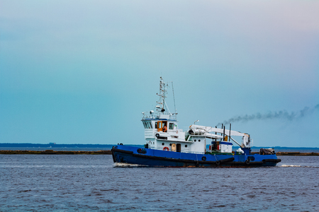 Blue tug ship moving to the cargo terminal. Industrial services Stock Photo