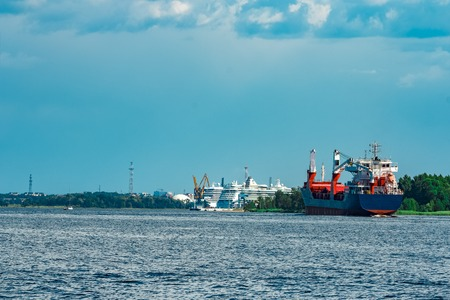 Merchandise import. Large blue cargo ship moving to Riga port