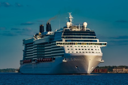 Giant white passenger ship moving past the port on a clear day Stock Photo