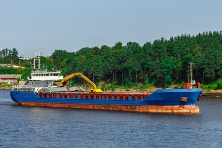 Blue cargo ship with long reach excavator moving to the port