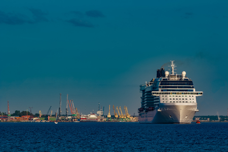 Giant white passenger ship moving past the port on a clear day Banco de Imagens