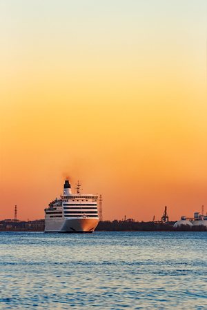 White passenger ship moving against the orange sunset sky