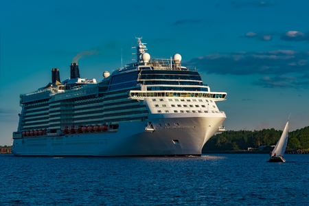 White giant brand new passenger ship moving in clear summer day