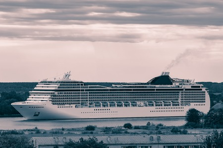 Large cruise liner sailing past the cargo port. Monochrome 写真素材