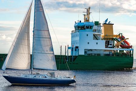 Blue sailboat traveling against the cargo ship in Riga Foto de archivo
