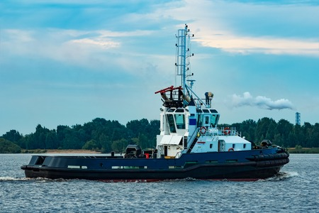 Black tug ship moving to the cargo terminal. Industrial service