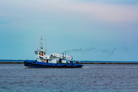 Blue tug ship moving to the cargo terminal. Industrial services Stock fotó