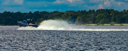 Grey speedboat moving fast by the river in Latvia. Water sport