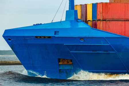 Blue cargo container ship fully loaded underway