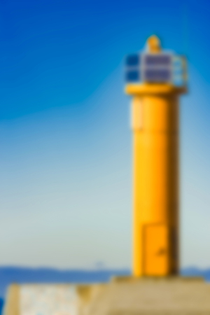 Yellow lighthouse - soft lens bokeh image. Defocused background