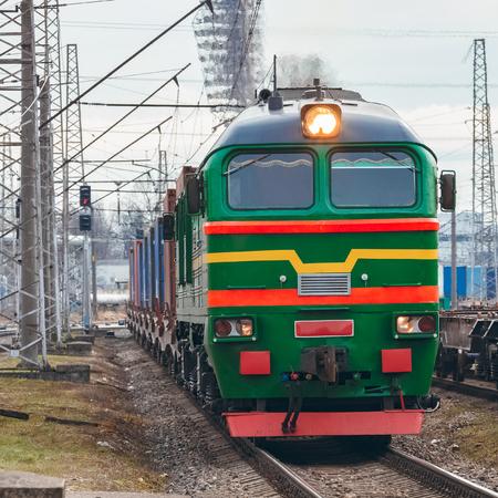 Green diesel cargo locomotive. Freight train in action