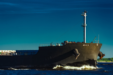 Black bulk carrier moving at evening to Baltic sea Stock Photo