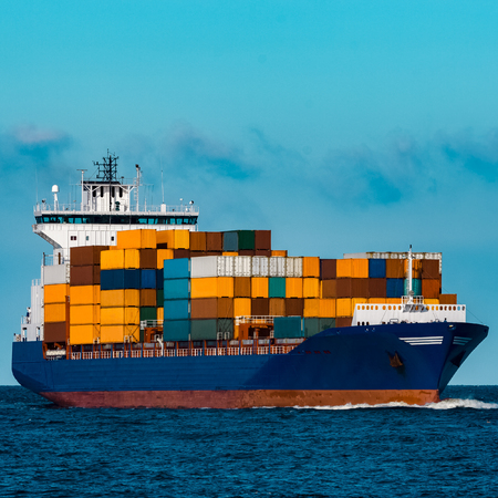 Blue container ship in travel. Logistics and freight industry Stock Photo
