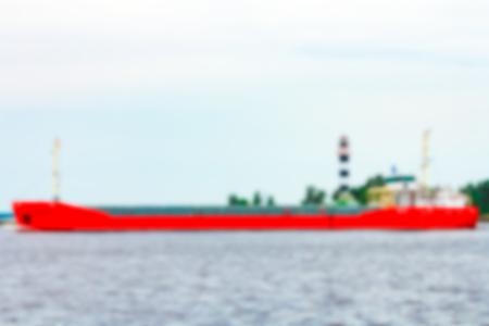 Red cargo ship - soft lens bokeh image. Defocused background
